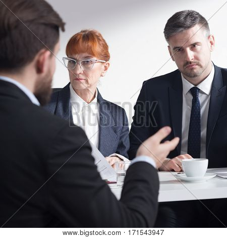 Professional recruiters listening to a job applicant in suit