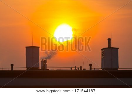 Smoking chimneys of the house at winter sunrise