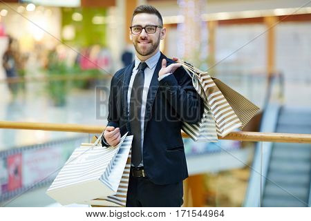 Happy businessman in suit holding paperbags