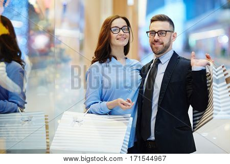 Wealthy shoppers with paperbags looking at camera in shopping-center