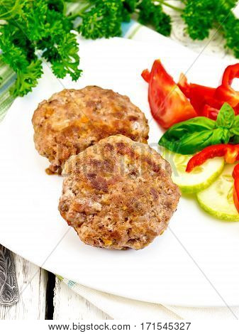 Cutlets stuffed with spinach and eggs in a dish, a salad of tomatoes, cucumber and pepper, basil and parsley on the background light wooden boards