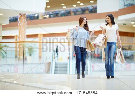 Young females with paperbags moving down shopping-center and talking