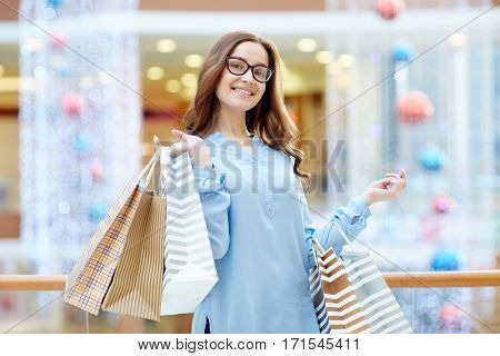 Pretty shopper looking at camera in shopping-center
