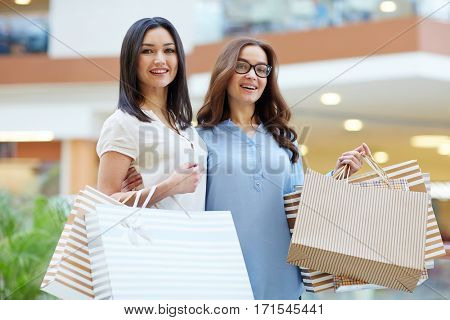 Two friendly shoppers with paper-bags in the mall