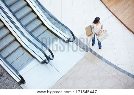 Young shopper with bags standing by escalator in the mall