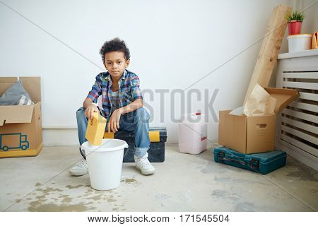 Little boy with sponge and bucket of water sitting on tool-box