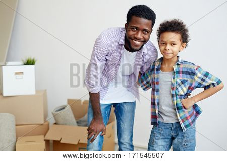 Affectionate man and his son just relocated to new house or flat
