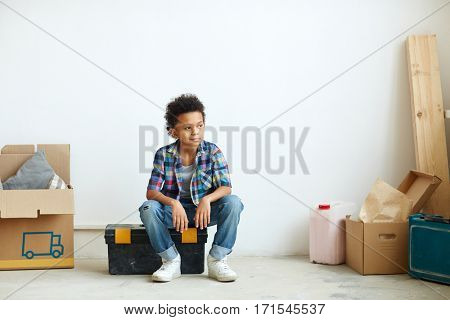 Little boy sitting on tool-box in his new room