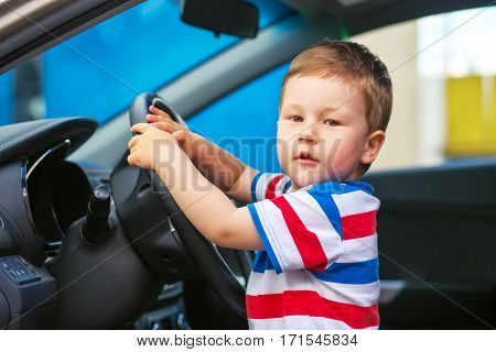 Cute little boy sitting in the car and keeps the wheel