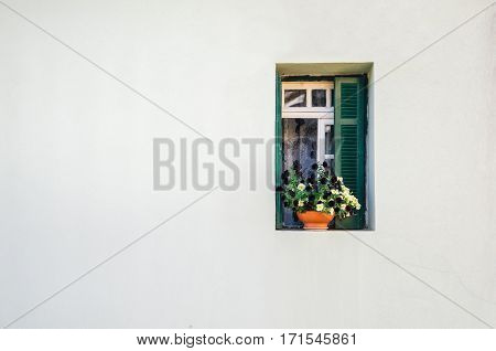 View of the white stone house and the small green window with the curtains and small pot of colorful flowers. Minimalism and free space for background concept.