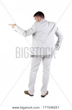 Businessman pointing at wall. rear view. Isolated over white .