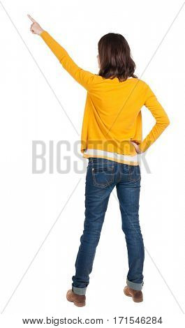 Back view of  pointing woman. beautiful brunette  girl in yellow pullover. Rear view people collection.  backside view of person.  Isolated over white background.
