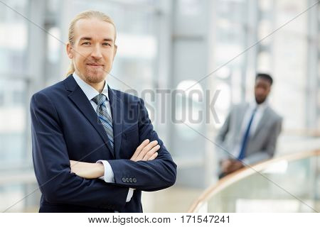 Business leader in suit crossing his arms on chest