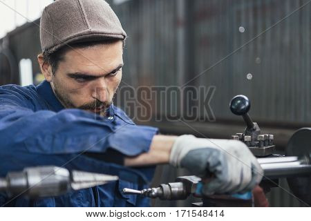 Bearded man in cap working with iron details