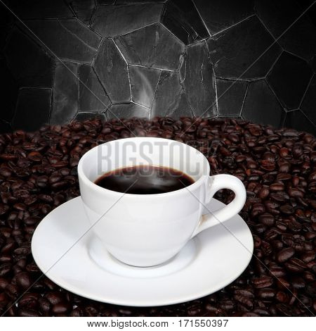 Black coffee in cup and coffee beans with smoke on granite wall background.