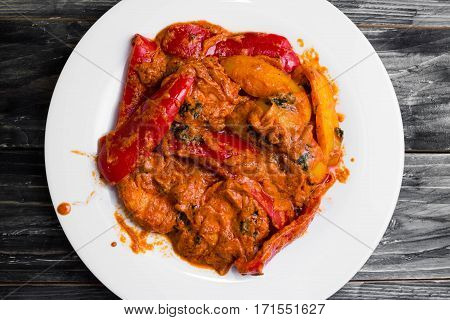 Bigus with chicken breast and bell pepper on a wooden table in rustic style