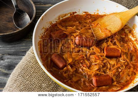 Bigus with sausages in a frying pan on a wooden background in rustic style