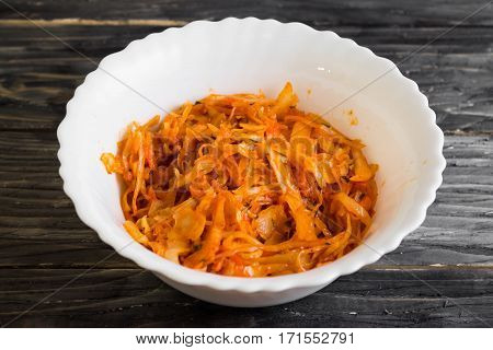 Braised cabbage in a white bowl on a wooden table in rustic style