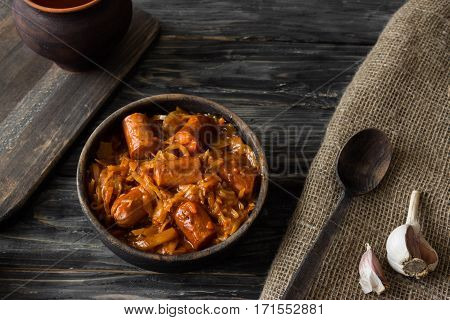 Bigus with sausages in a wooden bowl on a rustic background
