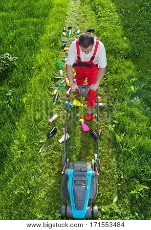 Man working against nature - concept with plastic spewing lawn mower view from above