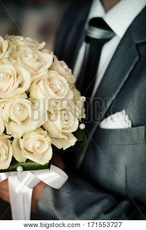 Stylish groom holding a tender beige wedding bouquet