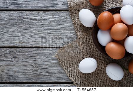 Poultry farm concept. Bowl with fresh brown and white eggs on burlap textile at rustic wood background with copy space. Top view on sacking. Rural still life, natural organic healthy food.