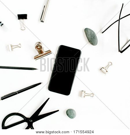 White office table desk with supplies. mobile phone glasses scissors and office supplies on white background. Flat lay top view office table desk.