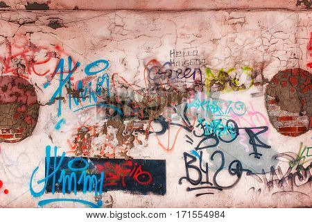 Wall and graffiti. Unreadable inscriptions in different colors.