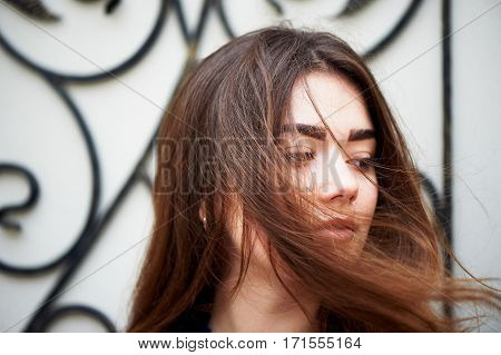 The wind in your hair. Young girl looking at the camera. Long dark and brown eyes .