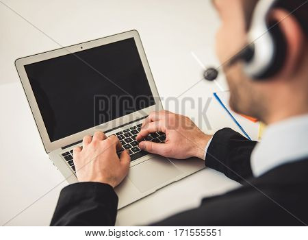Cropped image of attractive businessman in suit and headset working with laptop in office