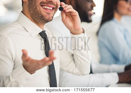 Cropped image of attractive business people in suits and headsets smiling while working in office