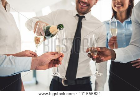 Cropped image of successful business people drinking champagne talking and smiling while celebrating in office