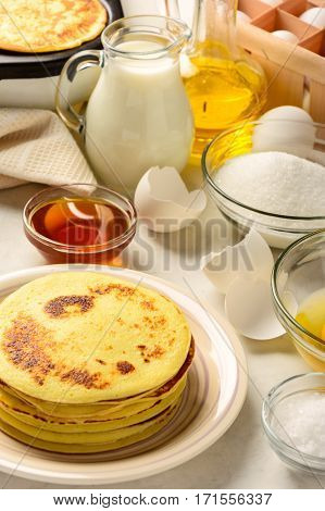 Pancakes and ingredients for making pancakes on a white background