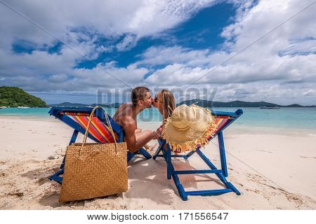Couple kissing on tropical beach in loungers at Thailand