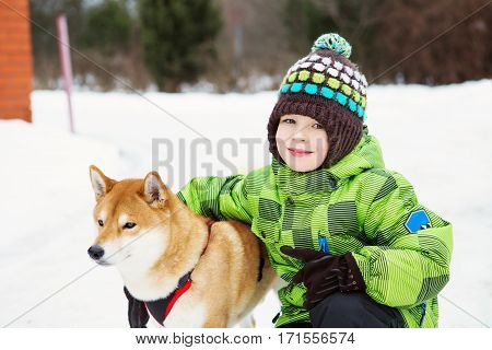 Boy With Shiba Inu Dog Outdoors In The Winter