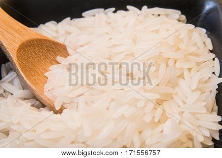 Closeup of the white rice with wood spoon focus at center