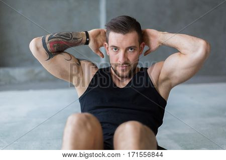 Young man workout in fitness club. Closeup portrait of caucasian guy making exercise, sit-ups and crunches for abs muscles, training indoors in window backlight