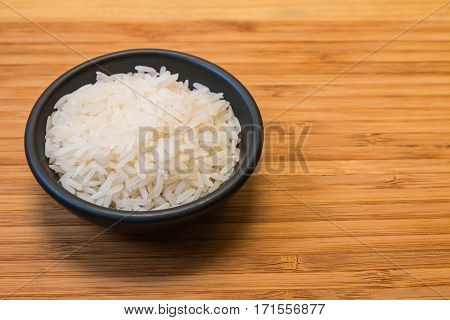 White rice in the black bowl focus at center of rice and space in right side