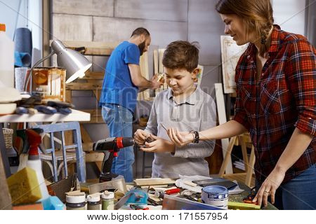 Parents and son tinkering together in workshop.
