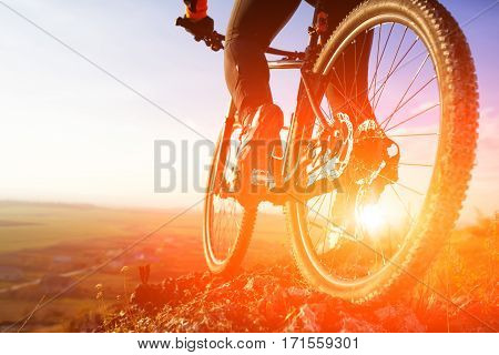 Closeup of cyclist man legs riding mountain bike on outdoor trail on hill. Landscape with sky, rocks and hill. Spring season. Extremal sport. Background with sunrise. Sport shoes. Travel in the countryside.