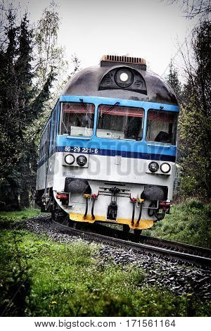 Blue and gray diesel train engine in the curve in rain