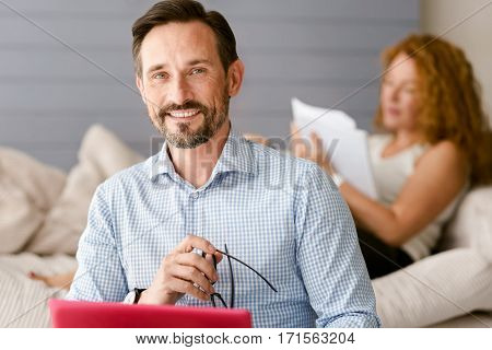 Full of enthusiasm. Positive handsome aged man sitting at home and holding the laptop and glasses while his wife working in the background