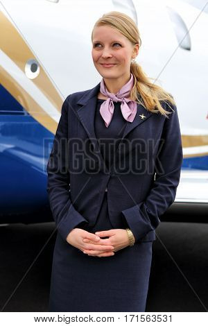 Stewardess in blue uniform by the aircraft body