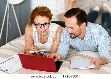 Exploring useful information. Smiling involved creative couple lying on the bed at home and using the laptop while sharing opinions and taking notes
