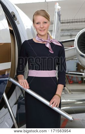 Uniformed blonde airhostess standing on the stair of small jet plane in the hangar