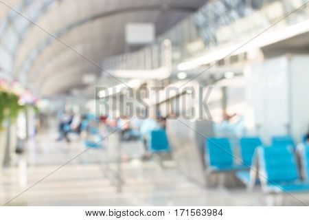 Blur background passenger waiting for flight at airport terminal with bokeh light with bokeh light