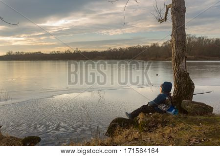boy sitting by the water in the early spring