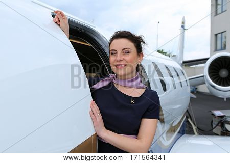 Brunette flight attendant looking out the open doors of the small jet plane