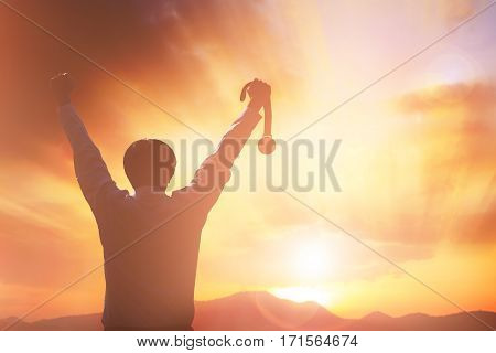 Silhouette business people raising hands and holding gold medal with sunset sky. victory concept.