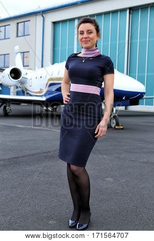 Whole figure of the stewardess standing in front of business jet plane